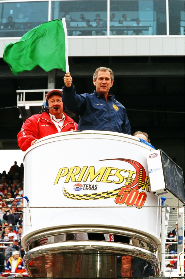 George W. Bush throws the green flag to start the Primestar 500 NASCAR Cup Series race at Texas Motor Speedway on March 28, 1999. Bush, then the Governor of the State of Texas, became President of the United States in 2000.