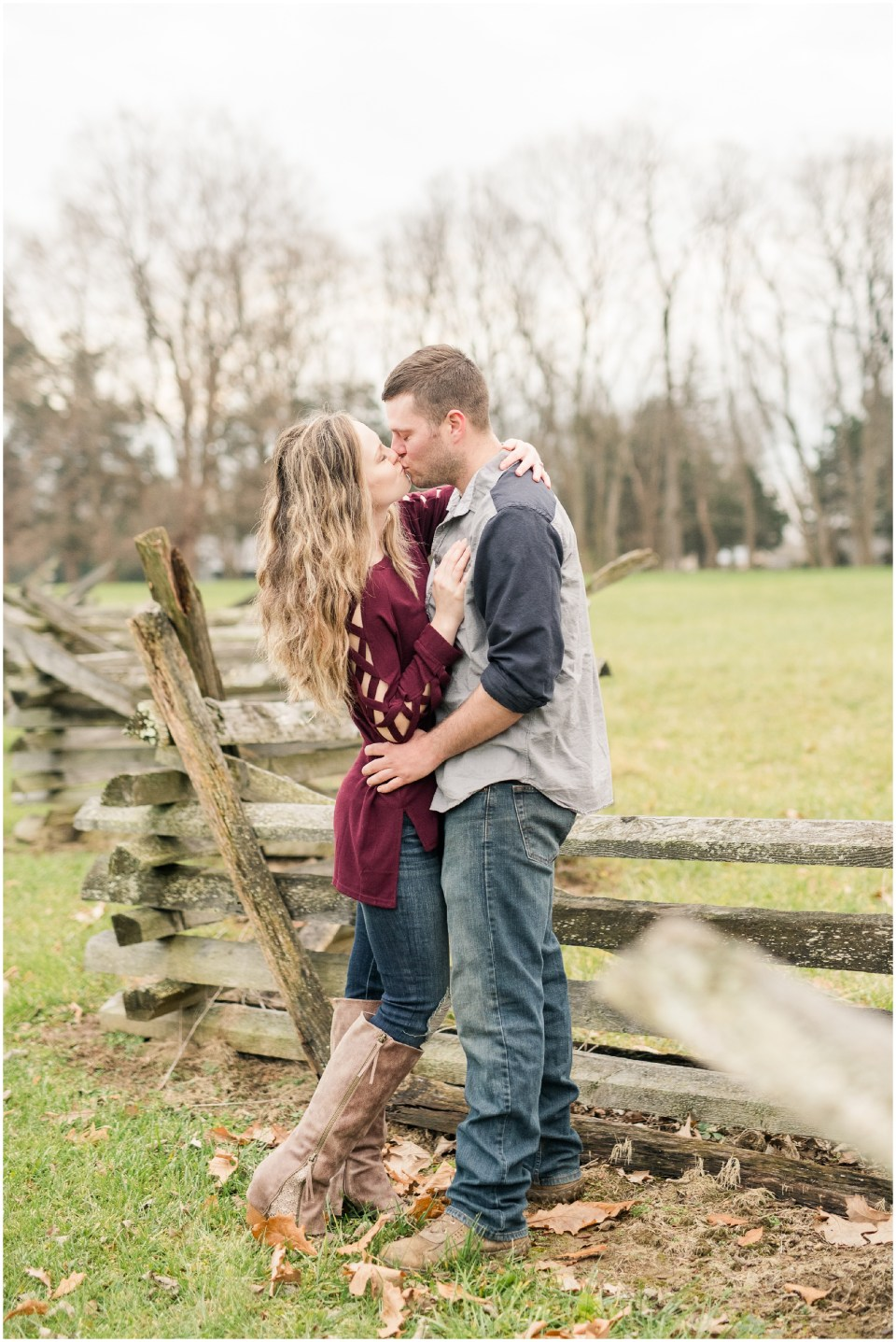 Engaged couple kissing in historic, Carriage Hill Metropark in Dayton, Ohio close to a fence in the wintertime.