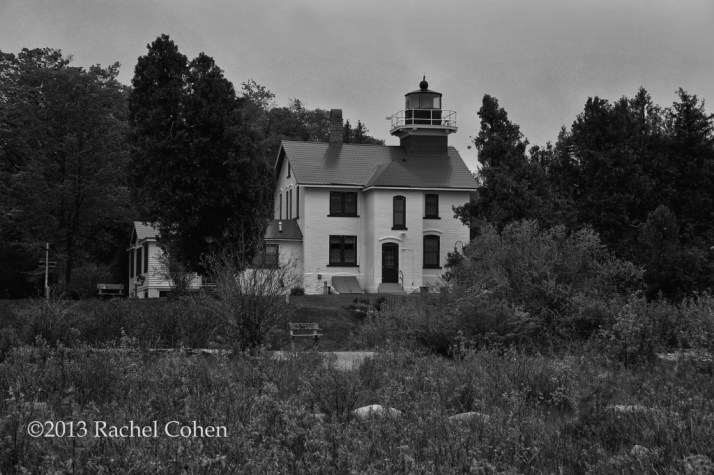 A side view of Grand Traverse Lighthouse as seen from the shore while dodging swarms of black flies and standing on large rocks.