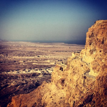 The side of Masada and the Dead Sea in the distance