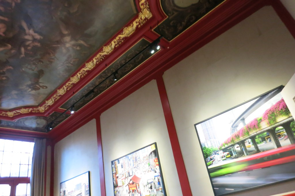 In this photo of the Huis Marseille Museum for Photography, you can see some of Martin Roemers' photographs and a bit of the ornately painted ceiling.