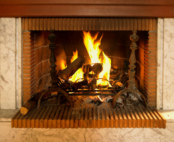 Log fire burning in fireplace with red brick surround