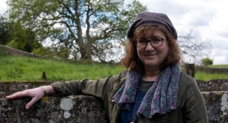 Debbie Young standing by a stone wall with a field beyond