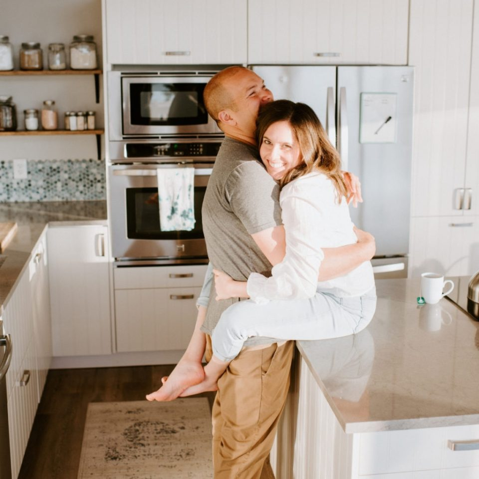 Husband and wife in playful embrace on the kitchen counter.