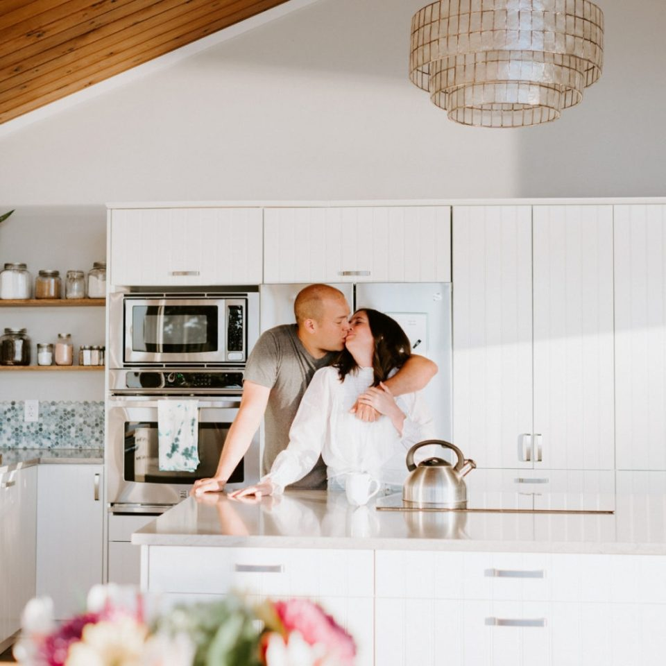 Husband and wife kissing in the kitchen.