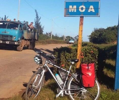 A bike in front of the sign for Moa on our cycling trip in Cuba