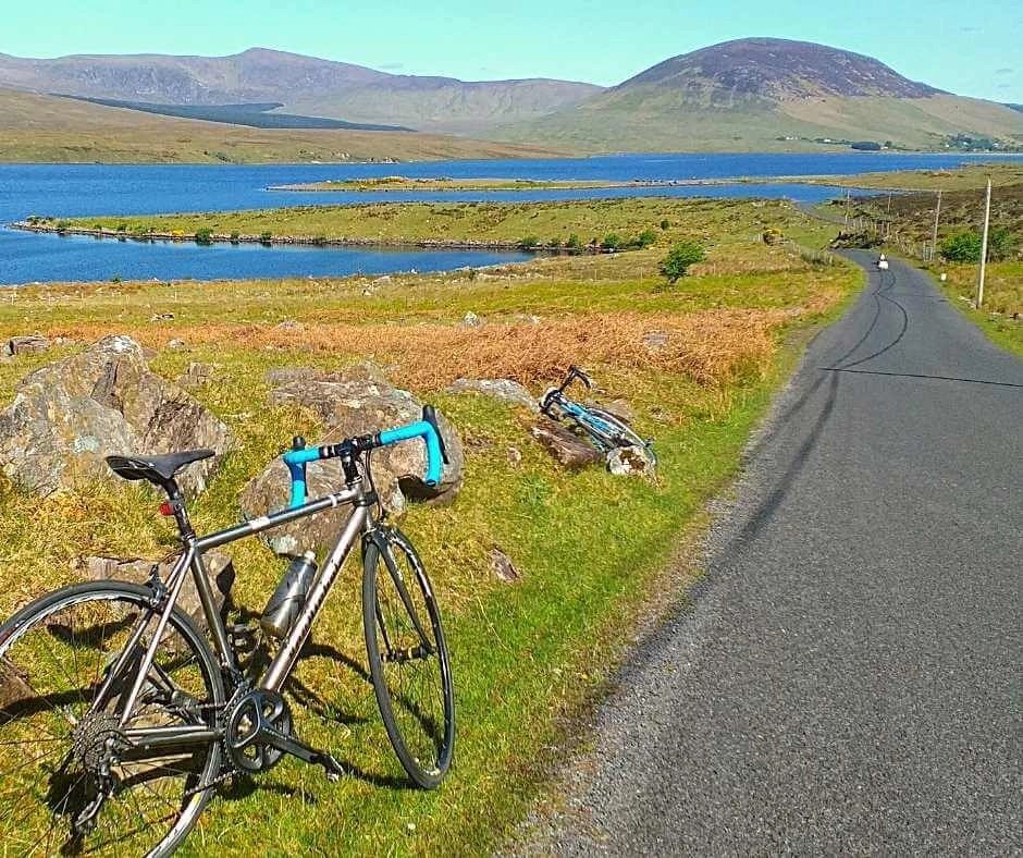Road bikes on the side of a rural road, a lake and mountains in the background on a sunny day in County Mayo Ireland