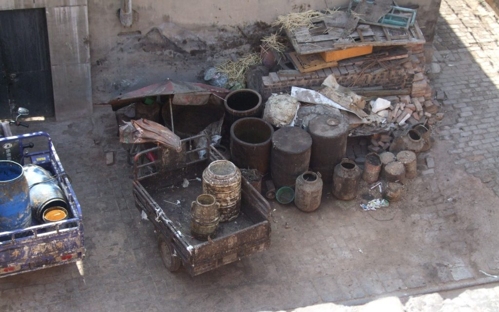 Seen from above: Two wagons are parked, with barrels on them of various sizes, all looking brown and filthy. Beside them is a cluster of more barrels, again in a range of sizes, some open, some closed. the ground is paved in brick, but damaged in places.