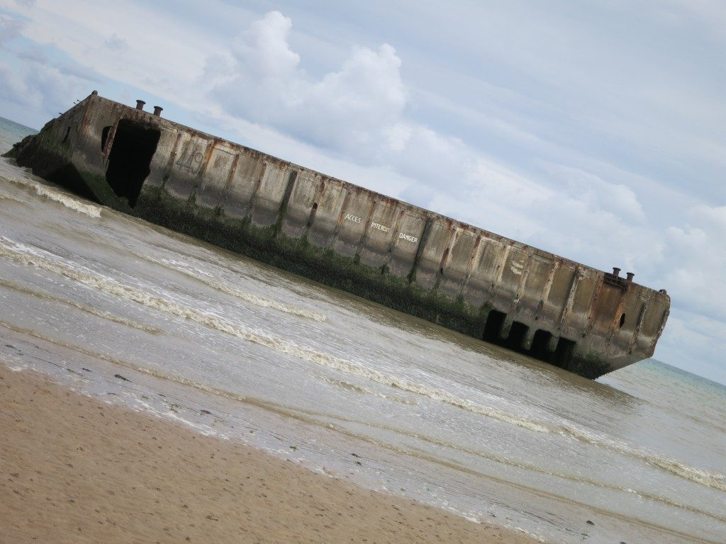 A huge horizontal thing seen from the beach, not far off the sand: it sits very high out of the water, flat on top, and looks like it is made of concrete.