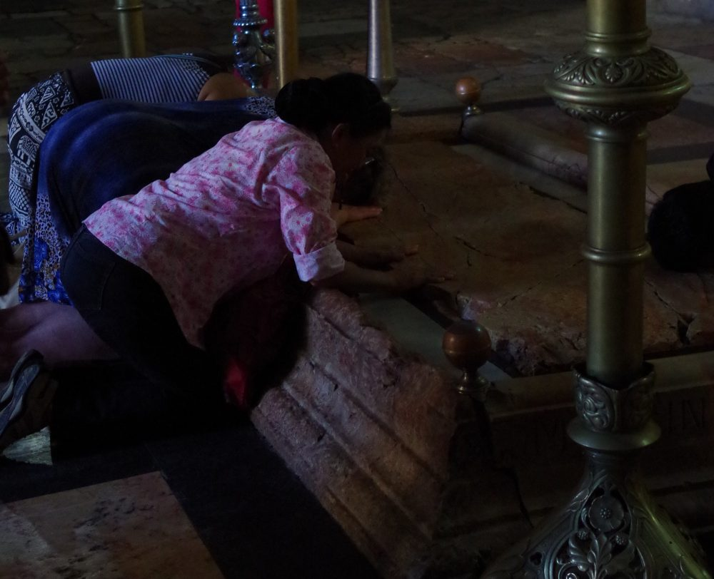 pilgrims praying at the rock where Jesus's body is said to have been washed, in the Church of the Holy Sepulchre on the Via Dolorosa
