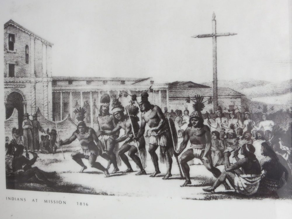 """drawing of Native Americans at Mission Dolore: Black ink on paper, says """"Indians at Mission 1816"""" at the bottom. 5 Native American men wearing just clothes around their bottoms and headdresses stand in a row holding spears. They appear to be dancing. Behind them many more Native Americans sit on the ground, watching them."""