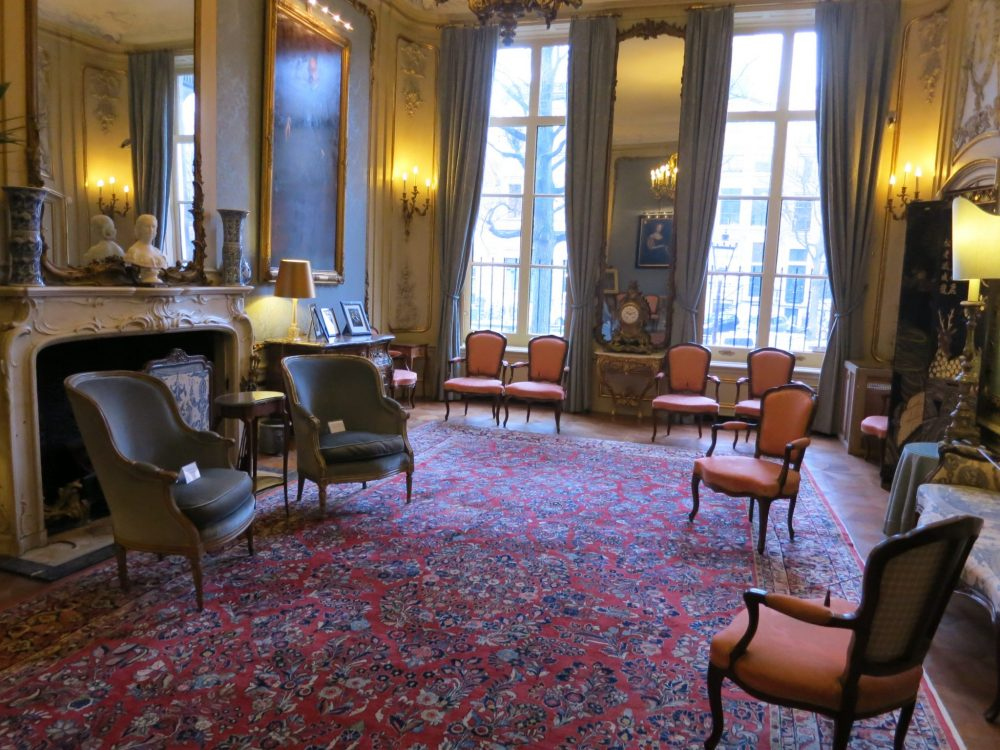 An elegant drawing room with dark red flowered carpet and a scattering of chairs at the Museum van Loon.