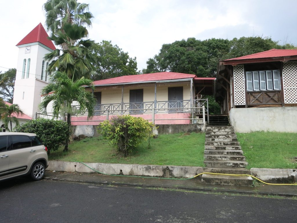The building is small, beige with a red roof, more like a house than an office, with a small porch in front. It sits on a grassy rise with a parking lot in front. To the left the church tower is visible beyond a palm tree. To the right only part of the neighboring house is visible, with painted shutters.