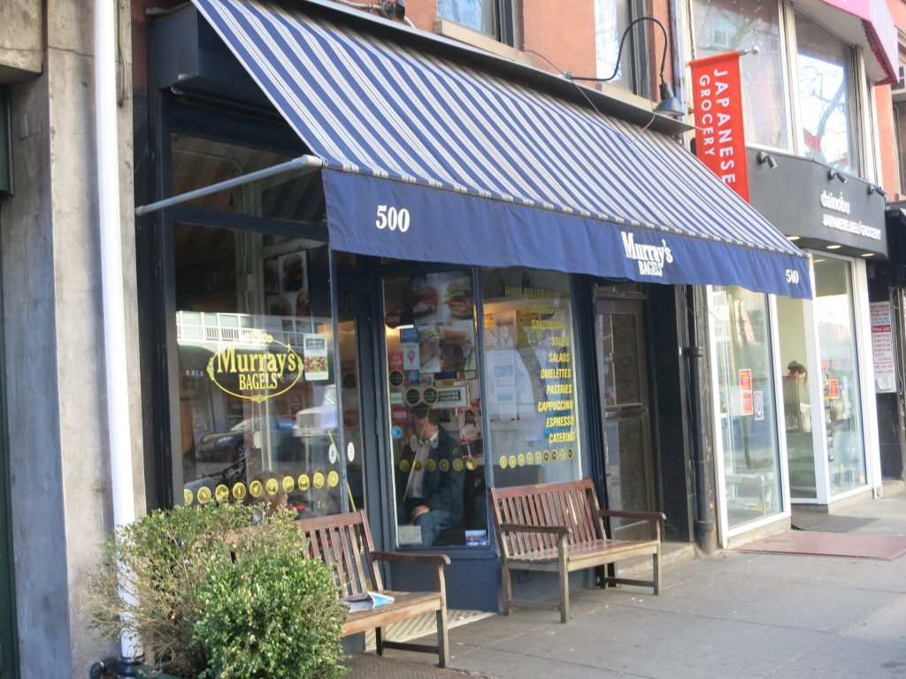 """A simple storefront: glass windows with a door between them, two benches in front outside. An awning, striped in blue and white, extends out above the entrance and both benches. It says """"500"""" """"Murray's bagels"""" and """"500"""" along its edge."""