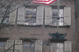 the Theodore Roosevelt Birthplace Museum exterior: a brownstone with an American flag fluttering in the breeze