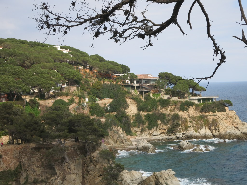 a view along the oceanfront coastal path in Lloret de Mar, showing a rocky coastline with houses here and there