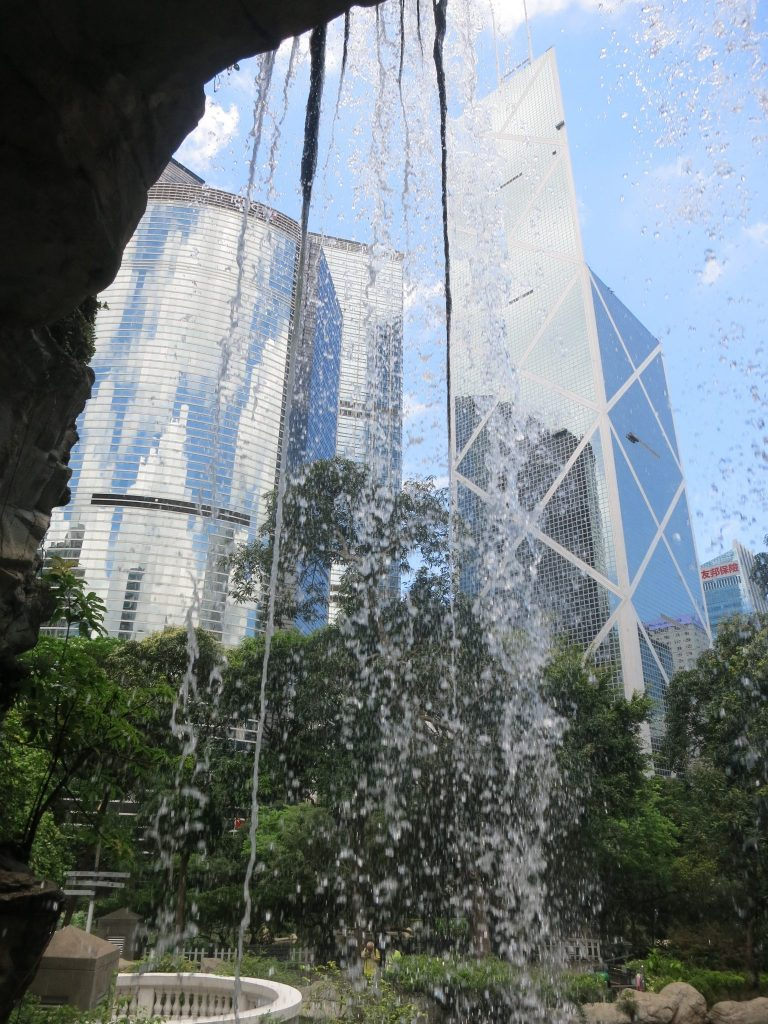 view of some shiny glass buildings, distorted by the waterfall