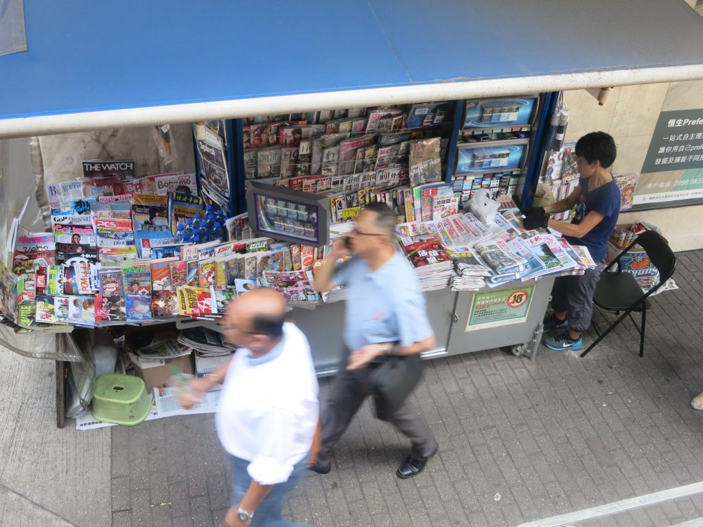 view down from a bus window, shows a newsstand in Hong Kong, with a woman working there, and pedestrians passing