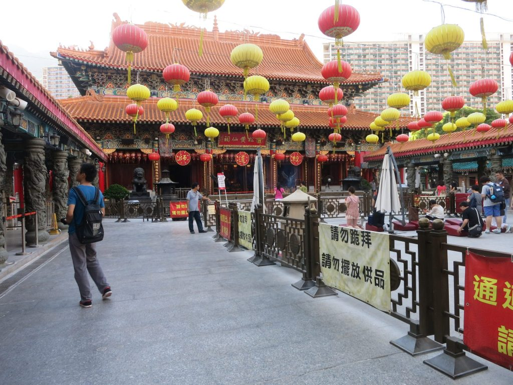 Temple in the background with the traditional roof line that curves upwards at the edges in red tiles. The open space in front has strings of paper lanterns hanging over it in lines of red and yellow. A few people are visible near the temple, praying. Behind the table some tall buildings.