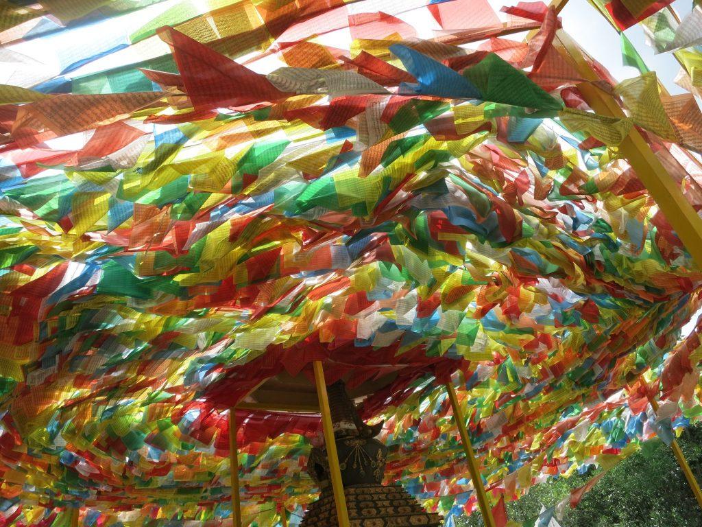 thousands of colorful triangular flags waving at a shrine on Pulau Ubin