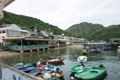 small fishing boats in the foreground, houses partly on stilts in the background, with large balconies: on Lamma Island