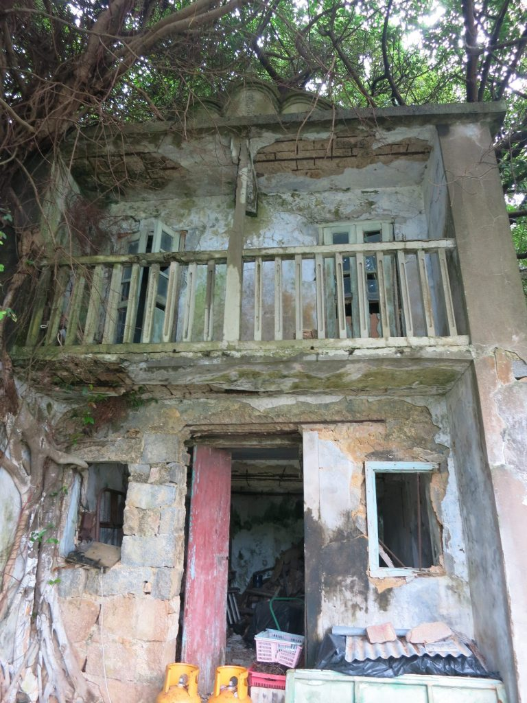a crumbling two-storey building with a balcony on the upper floor, on Lamma Island