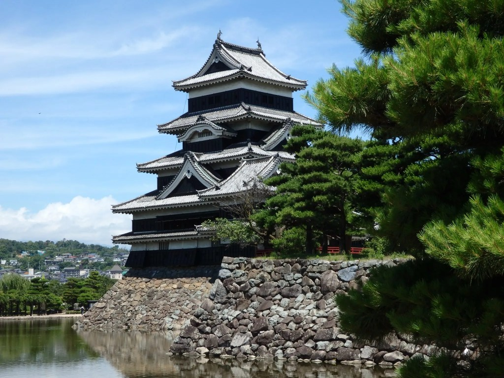 Matsumoto Castle appears to have five storeys, and stands on top of a stone wall above a moat