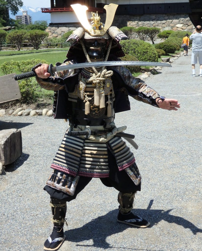 A man in full samurai armor blocks entrance with his sword, in front of Matsumoto Castle.