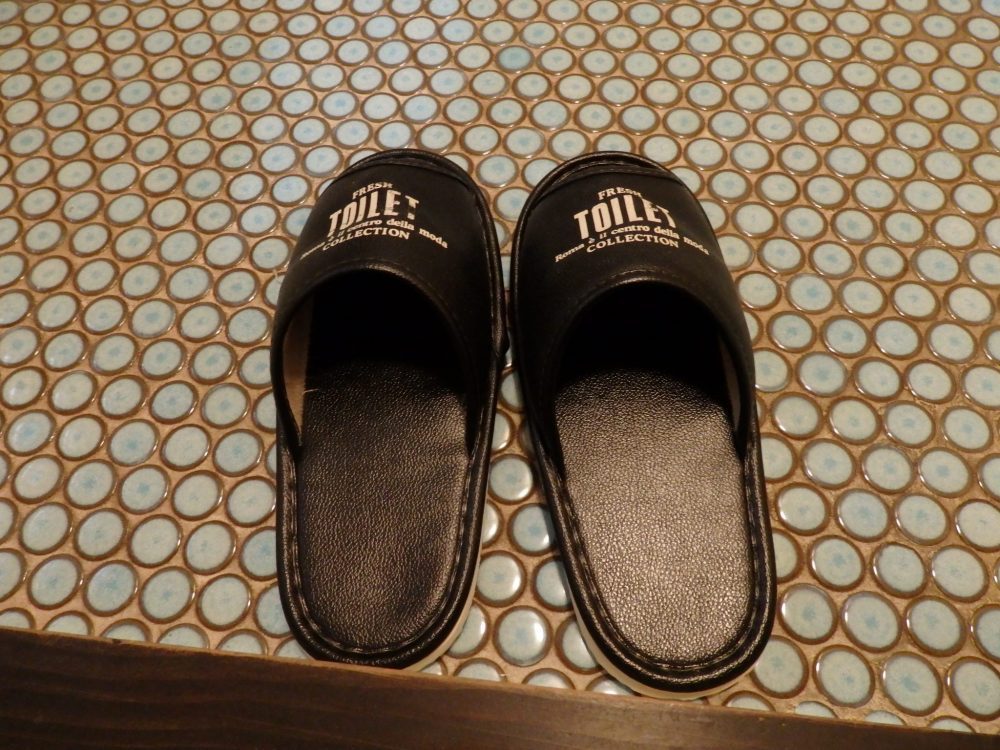 A pair of brown vinyl slippers on a rubber mat. The slippers say TOILET on each one.
