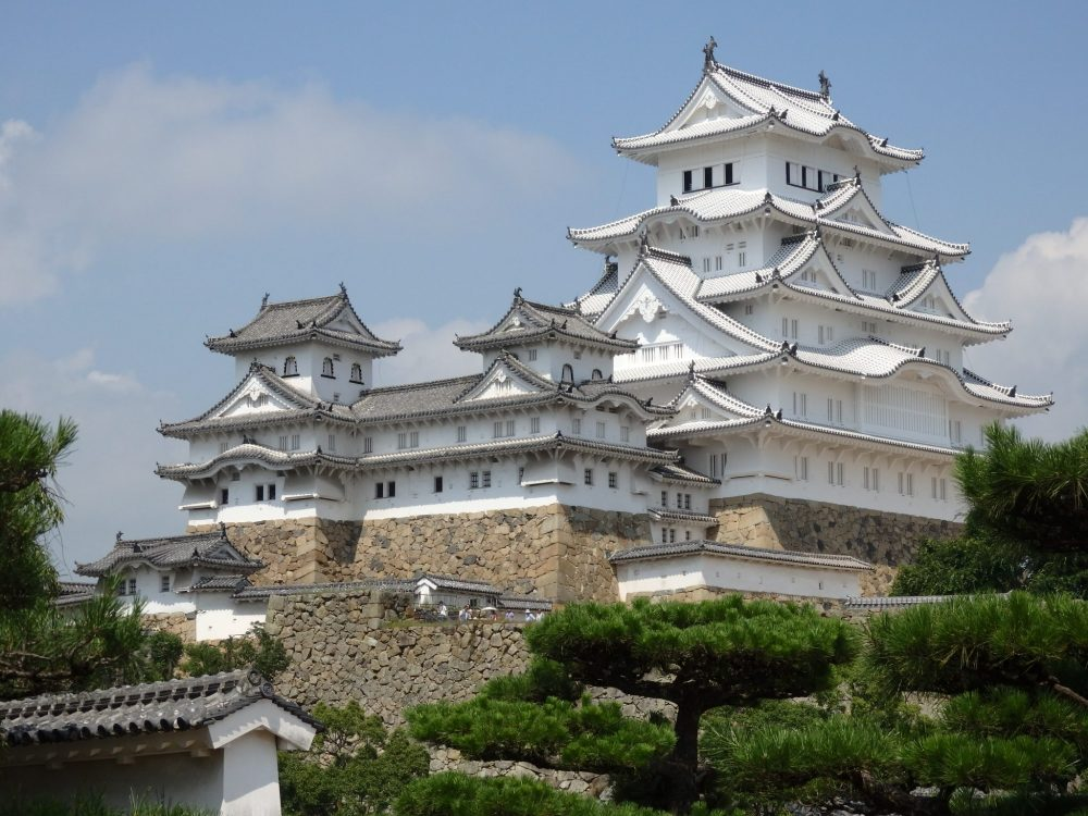 Things to do in Himeji: the ornate, enormous, white Himeji Castle looms. It has one main part that is taller than the rest, with curved white roofs and gables on every level. A wing in front is also white, but has fewer stories and a gray roof.