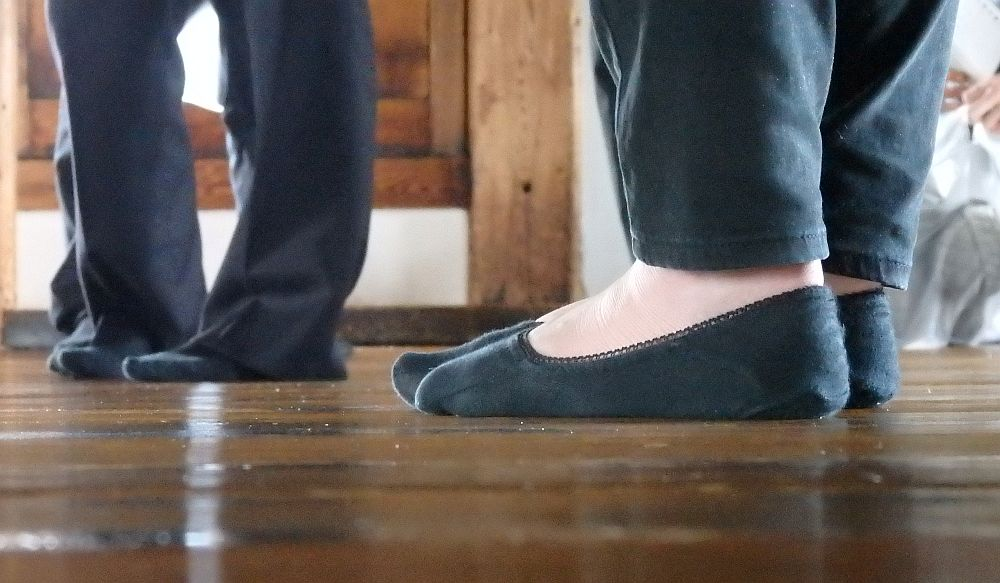 seen from floor level: a wooden floor and feet in black socks. In the distance, blurry, another pair of feet in socks is visible. Barefoot in Japan: a bumbling fool