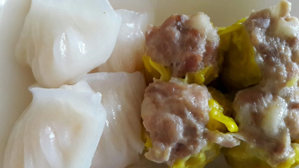 On the left: white steamed dumplings. On the right: pork balls partially wrapped in some sort of green leaf.