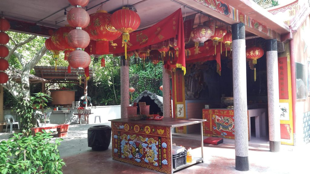 shrine with colorful lanterns and paintings decorating the altar, on Pulau Ubin in Singapore