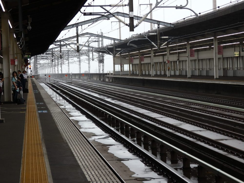 view of Japan Rail train tracks, looking down the tracks into the distance, as seen from a station platform.