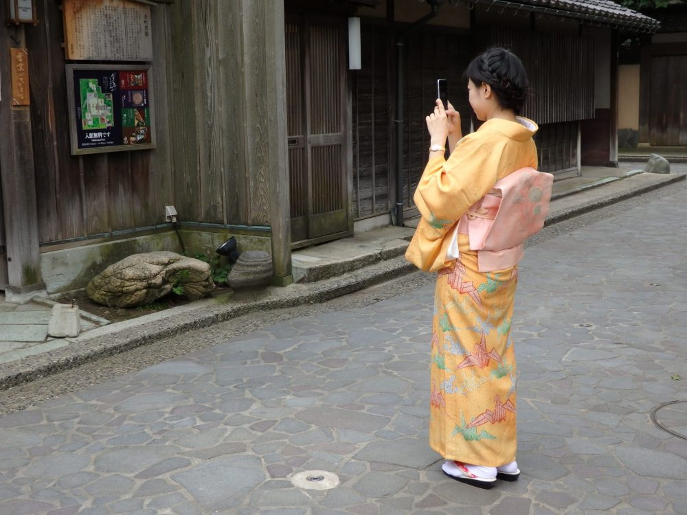 a girl in traditional clothing takes a picture with her mobile phone. She is angled away so her face is not visible, but the kimono is pale yellow with green and pink images of paper art birds. Is Kanazawa worth a visit?