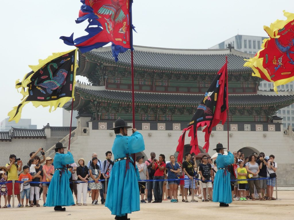 Guards carry flags during the changing of the guard ceremony at Gyeongbokgung Palace in Seoul, Korea