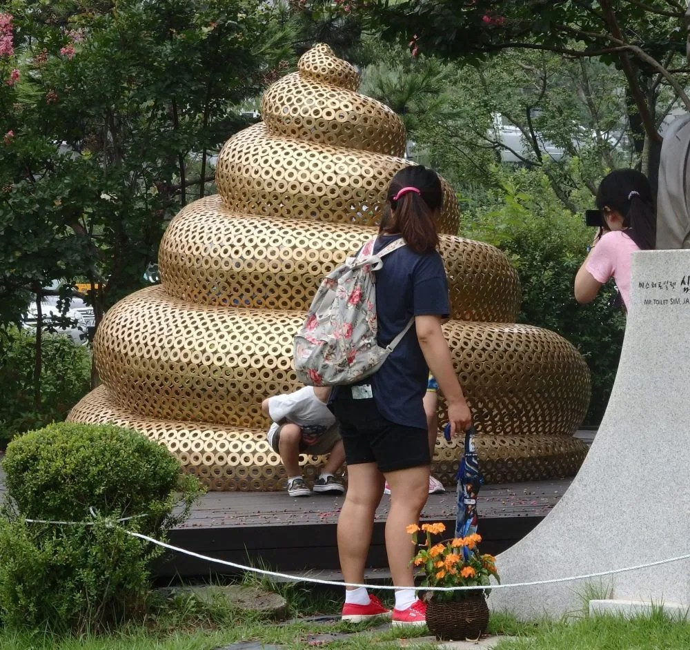 Visitors pose in front of the golden turd statue in front of the toilet museum.
