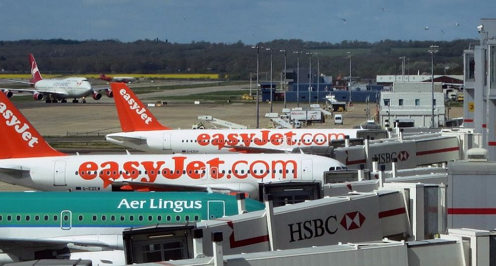The jets are parked at a gate. Visible are two easyJet planes and an Aer Lingus plane. Behind them a 747 approaches from the runway.