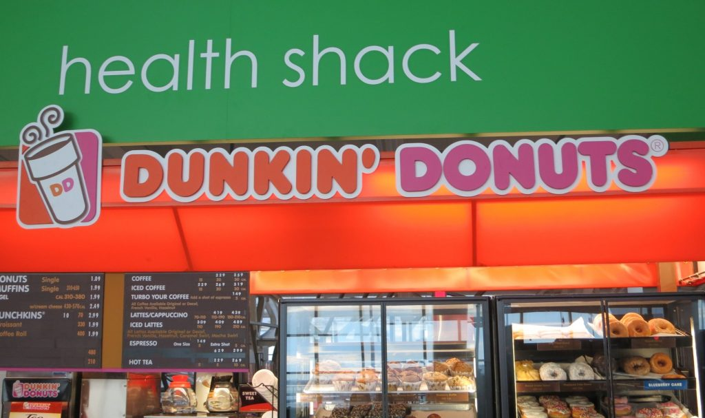"""A Dunkin Donuts sign under a sign reading """"health shack"""" at Kennedy Airport in New York CIty"""