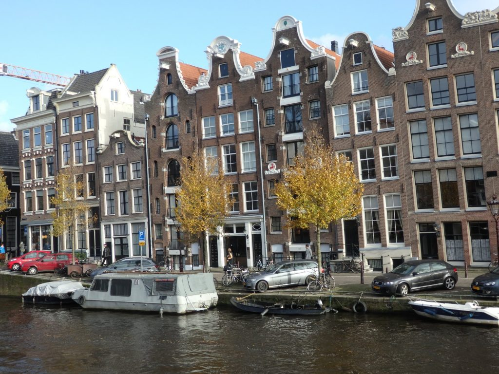 A row of typical Dutch row houses: tall and narrow, most of them are three windows wide and five or six stories high with pretty decorative gables at the top. In the foreground, the water of a canal and a few boats moored along its side.