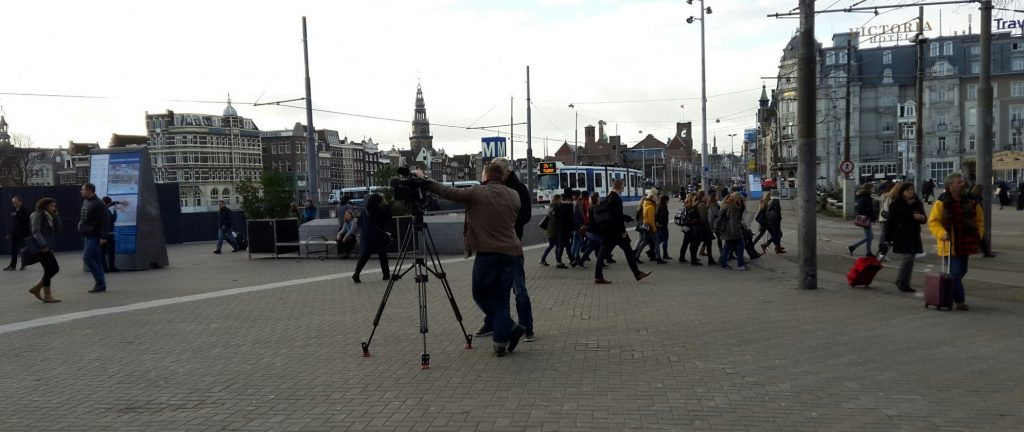 Two cameramen wait for me outside the Amsterdam train station. They stand in a clear open space next to a tripod with a big camera on top. People walk in various directions behind them, some dragging luggage. Buildings in the distance show that it is Amsterdam.
