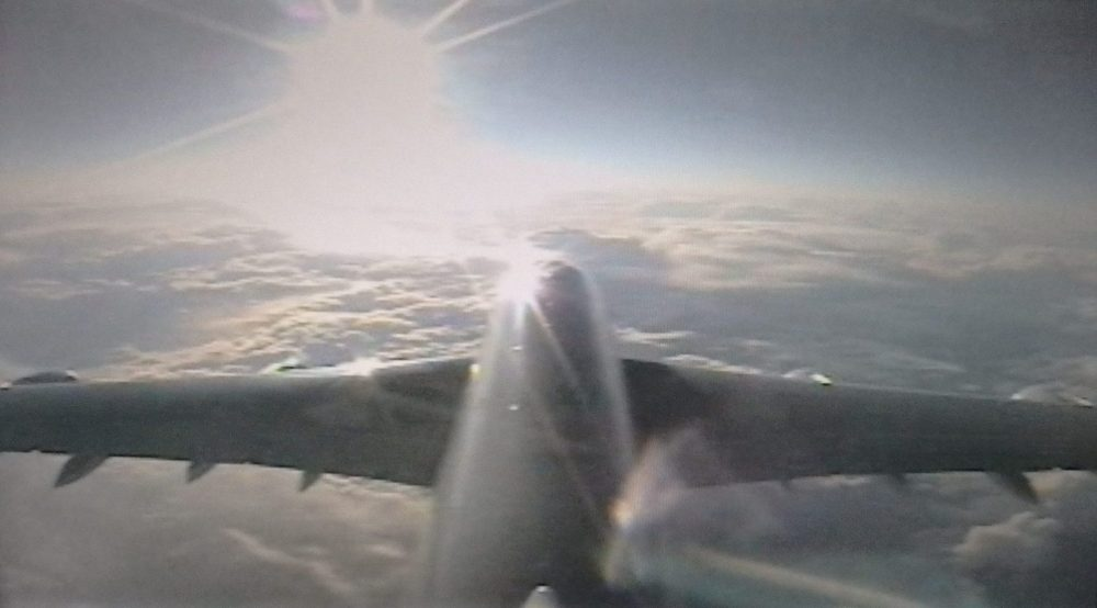 This is a fuzzy view of the airplane, looking forward from the tail. The sun is at 11:00 off the front, and underneath the plane are fluffy clouds.
