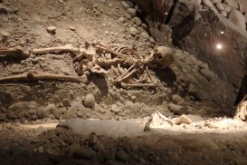 This grave was left in place inside the excavation. A mirror above the skeleton allows visitors to view it.