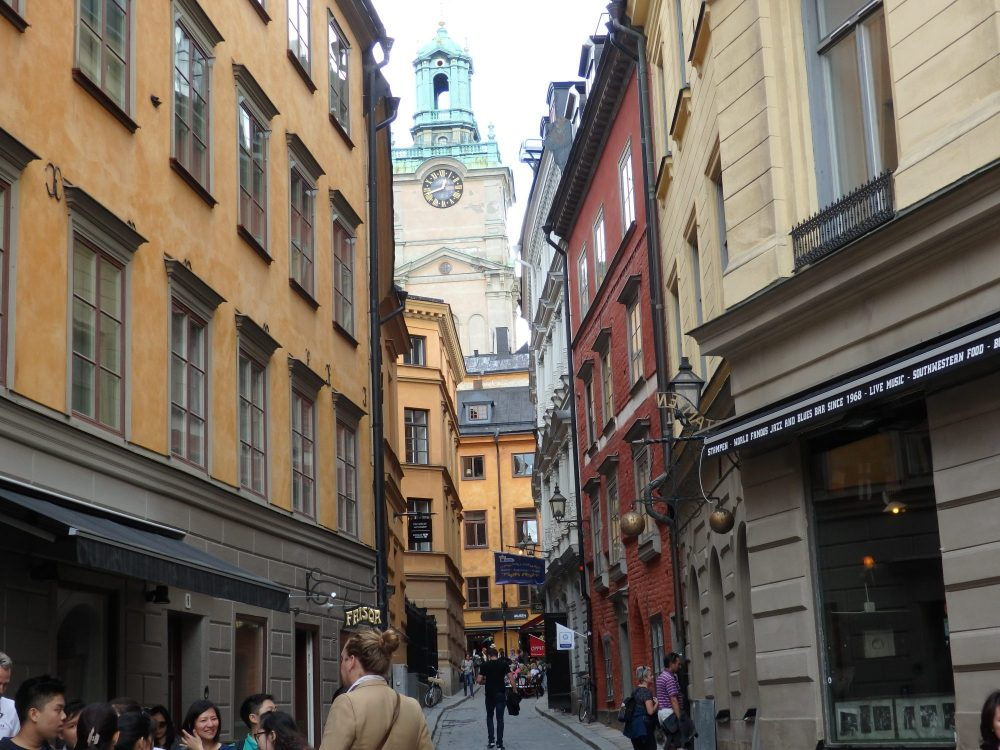a narrow street in the oldest part of Stockholm, Gamla Stan. Older apartment buildings on both sides, and a clock tower of a church visible down the street.