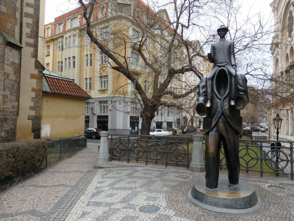 In a small square, with apartment buildings surrounding it, next to a tree, the statue depicts a man, his feet submerged in water? mud?, carrying a smaller man on his shoulders. The man sitting on his shoulders looks like a normal man, in a jacket, wearing a hat. But the man doing the carrying has no head. Instead, the collar of his jacket gapes and no chest or head are visible: just a hole.