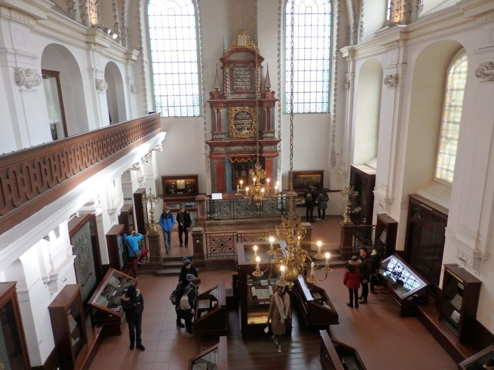 "The interior of the Klausen Synagogue, one of the Synagogues in Prague, seen from upstairs in the ""women's gallery."" A high, baroque structure frames what would have been the torah ark in the opposite wall. On either side of it is a large, arched window, letting in a lot of light. Below, on the ground floor, various display cases line the walls and down the middle. People are standing and looking at them here and there."