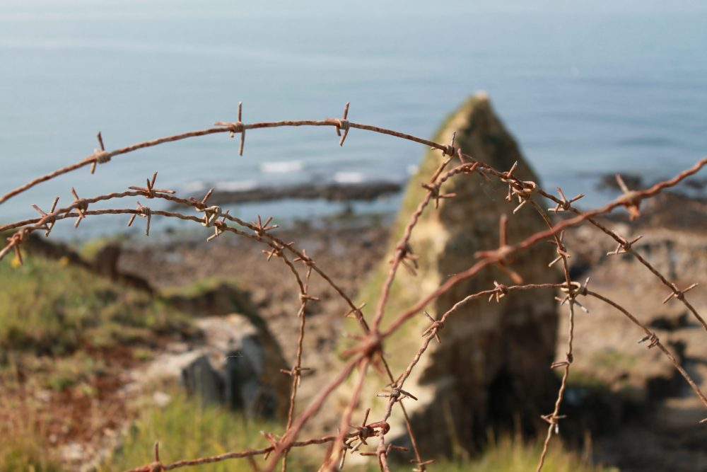 A view across a beach to the water, but what is in focus is in the foreground: a twist of barbed wire