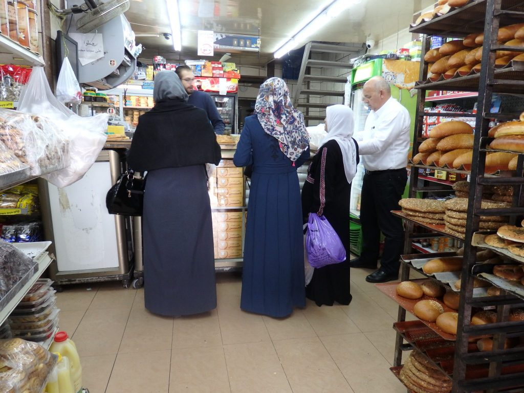 Three women being served at a bakery counter in East Jerusalem.
