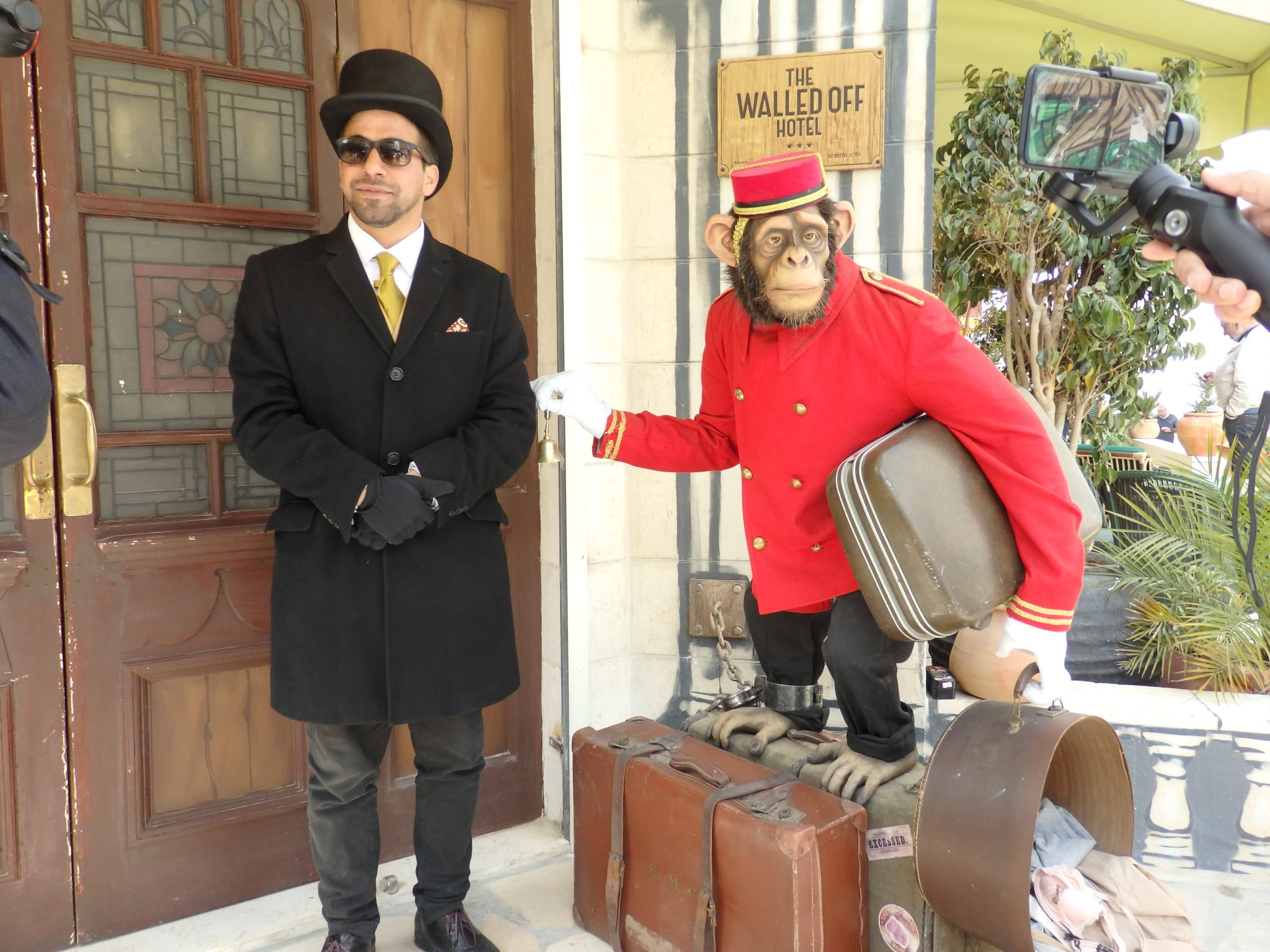 """At the entrance to the Walled Off Hotel, the doorman and the """"bellboy."""" Visiting Bethlehem"""