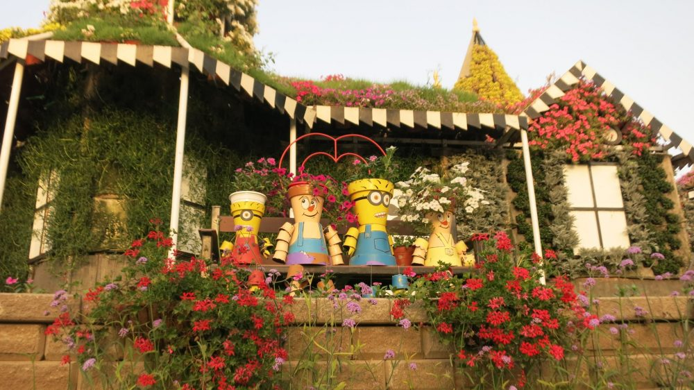 "Figures of people, made from flowerpots, sit on a bench in front of a flower-covered ""house"" at Dubai Miracle Garden."